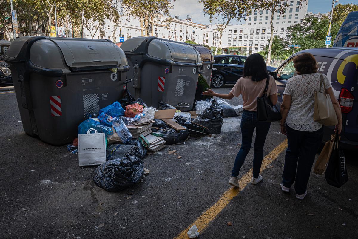 Dos mujeres comentan la sociedad acumulada junto a unos contenedores en el Eixample.