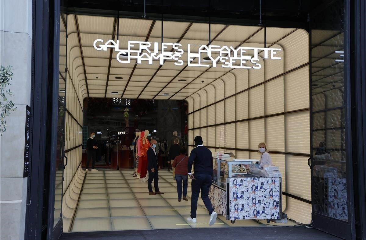 Clientes que esperan entrar en la emblemática tienda Galeries Lafayette de Avenue des Champs-Elysees