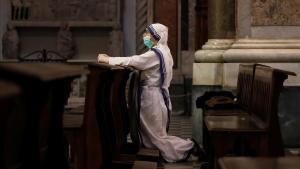 Una monja se protege con mascarilla durante una misa en la catedral de Nápoles.