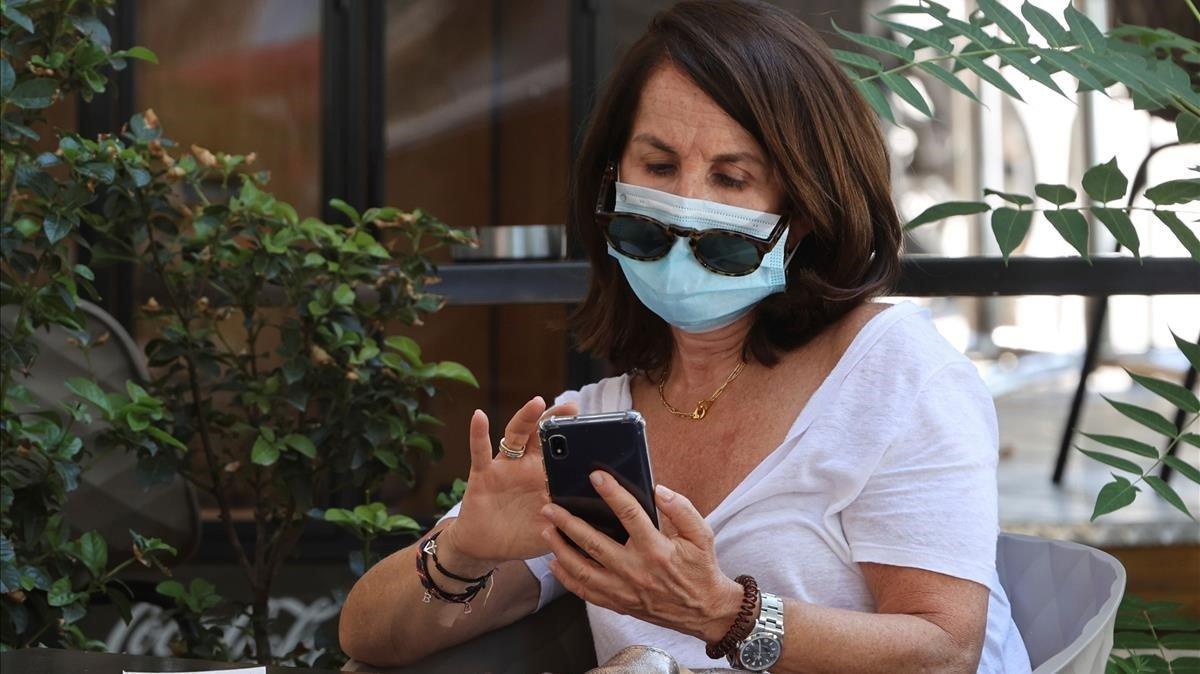 Una mujer con mascarilla revisa su teléfono en una terraza en Madrid.