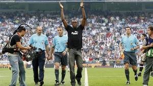 Usain Bolt saluda al público tras realizar el saque de honor en un partido en el Bernabéu