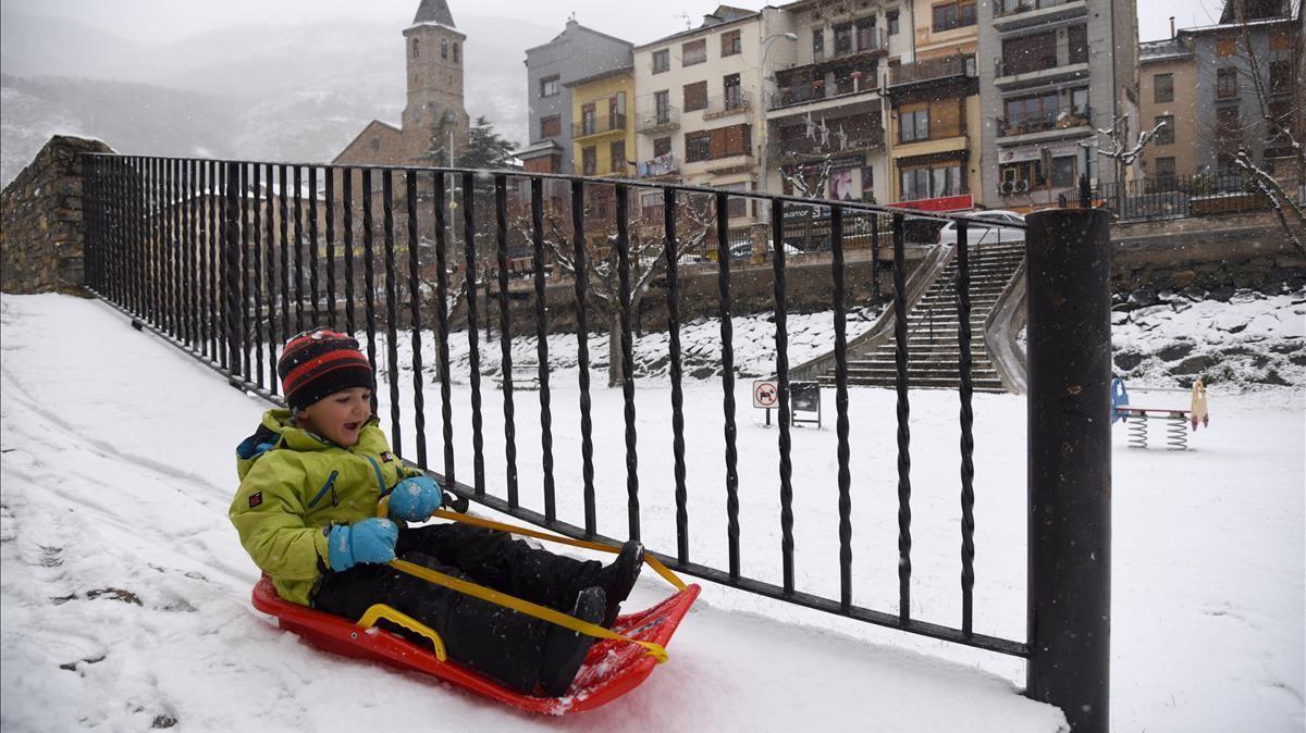 Un niño juega con un trineo en la nieve fruto de la borrasca Filomena  en Sort  Lleida