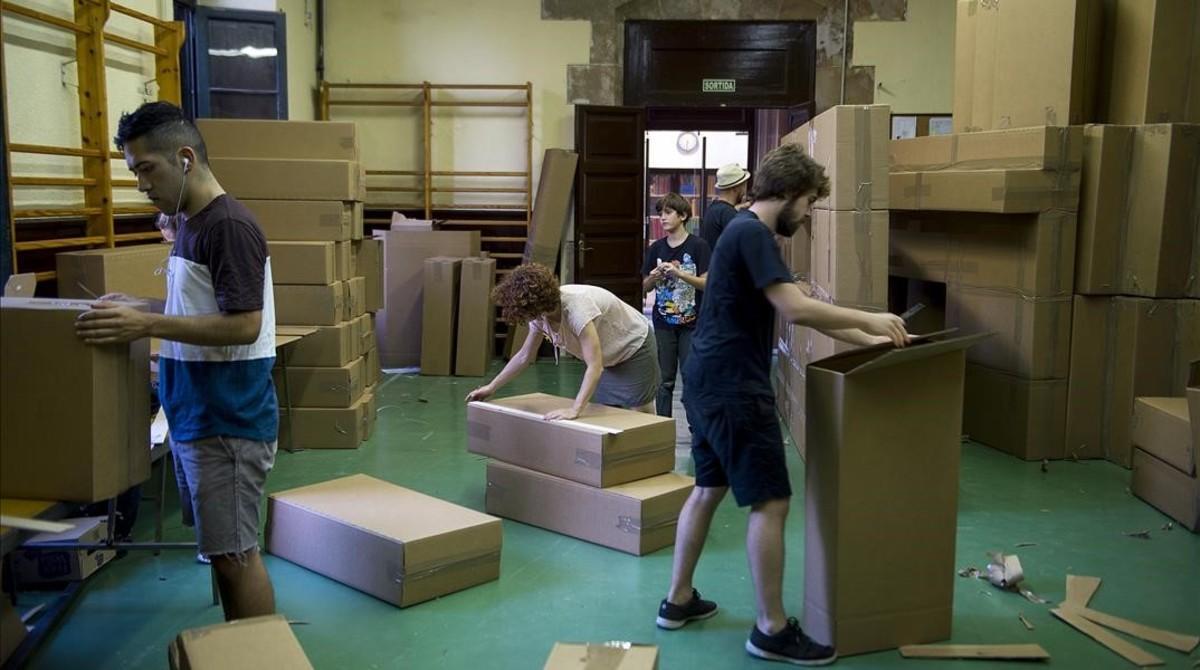 Los voluntarios montan las cajas de cartón para construir un puente y una réplica del conjunto monumental de la cascada de la Ciutadella.