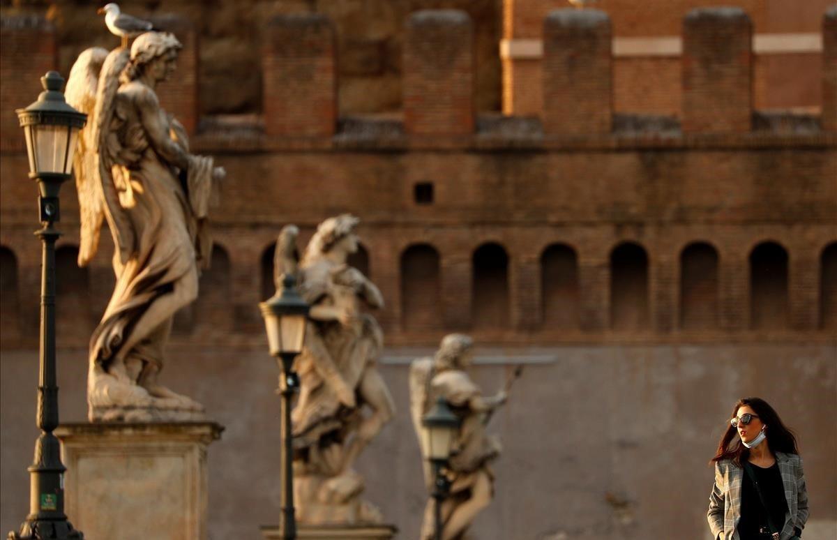 Una mujercamina sobre el Ponte Sant Angelo.