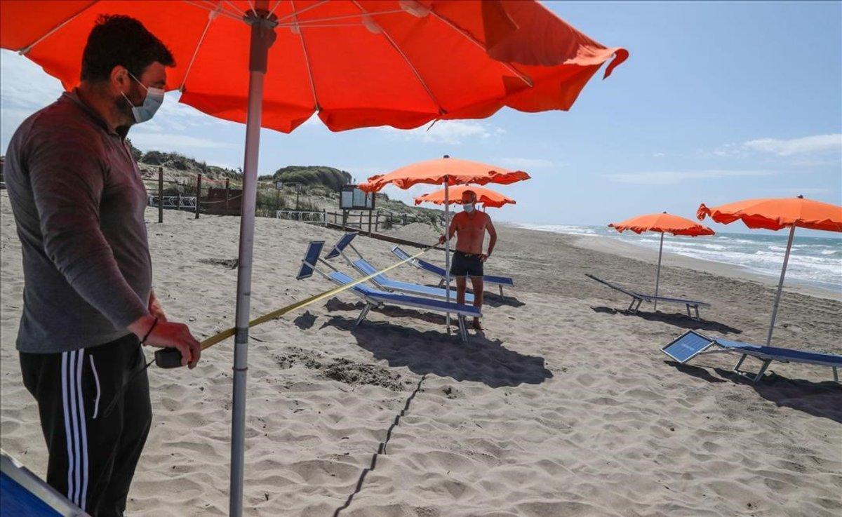 Dos trabajadores con mascarillas en la playa italiana de Copocotta, cerca de Roma.