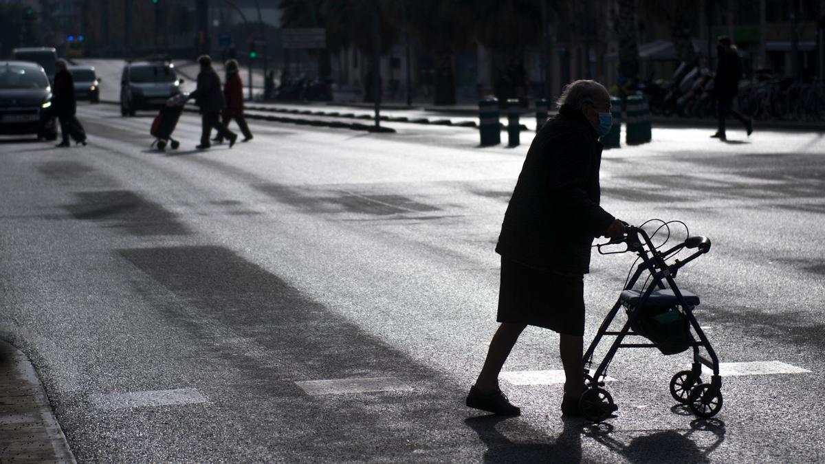 Una señora mayor cruza apoyada en su caminador la calle Marina de Barcelona.