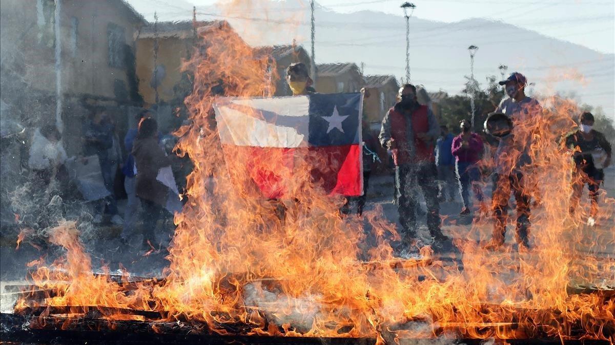 Un manifestante sostiene una bandera de Chile frente a una barricada ardiendo durante una protesta en Santiago de Chile, este lunes.