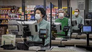 Cajeros protegidos por mamparas en un supermercado Mercadona de València, el 24 de marzo.