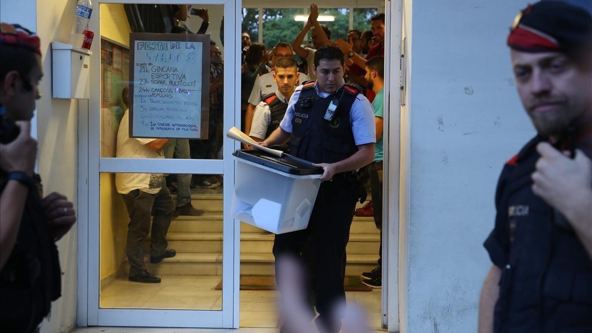 Un mosso se lleva una urna de un colegio durante el referéndum del 1-O.