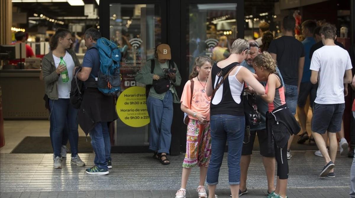 Turistas a las puertas de un supermercado de Barcelona.
