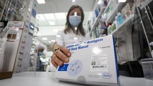 La farmacéutica Estela Rodríguez muestra un test de antígenos de cinco dosis en la farmacia del Monestir, en Sant Cugat del Vallès.