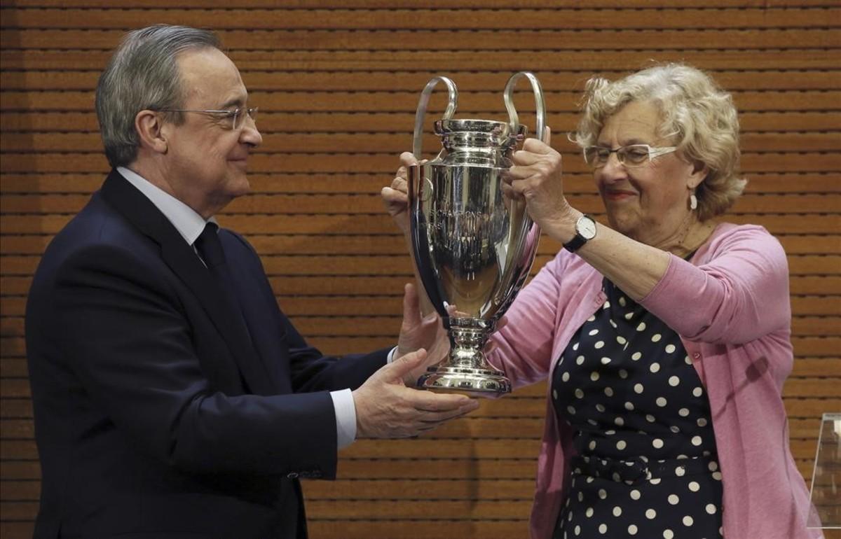 Florentino Pérez le entrega a Manuel Carmena, alcaldesa de Madrid, una réplica de la Champions.