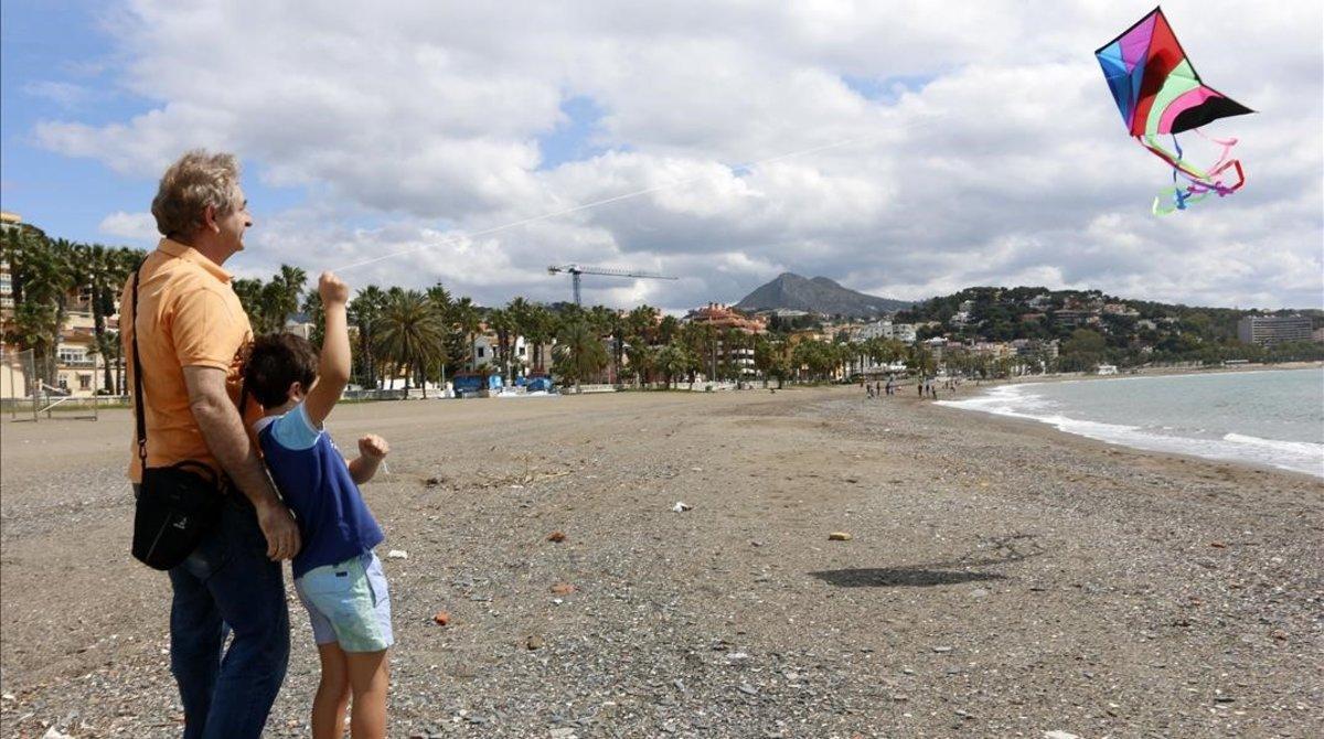 Un niño vuela una cometa junto a su padre en la playa en el primer día en el que los menores de 14 años pueden salirdurante el estado de alarma.