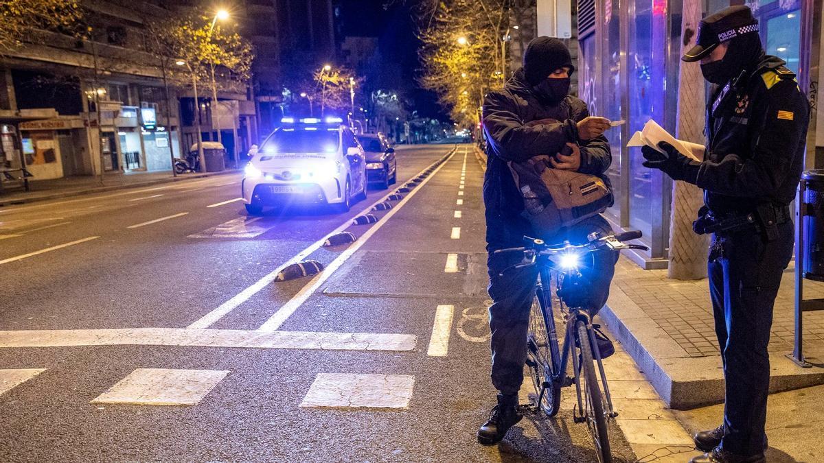 Un guardia urbano identifica a una persona que circula en bici fuera del horario permitido en la calle Urgell de Barcelona, el pasado 22 de enero.