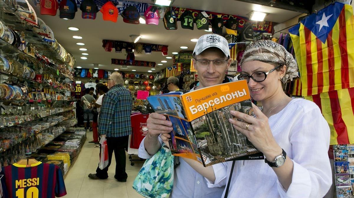 Dos turistas rusos consultan una guía de Barcelona en su idioma al salir de una tienda de suvenirs de la zona de Sagrada Família.