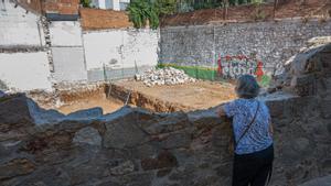 Una vecina contempla la obra del solar desde la parte de muro derribado