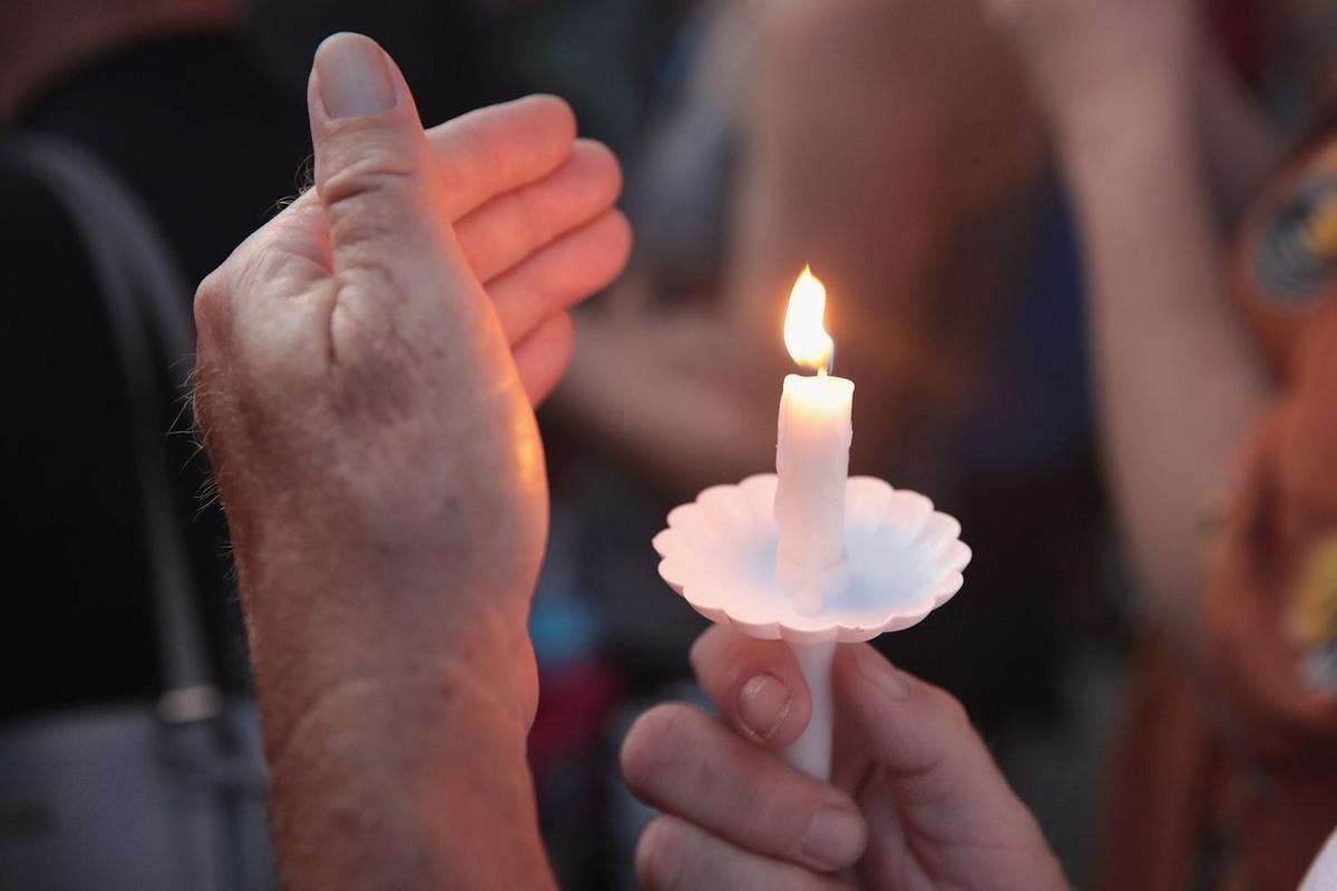 Un hombre enciende una vela por las víctimas del tiroteo en Ohio.