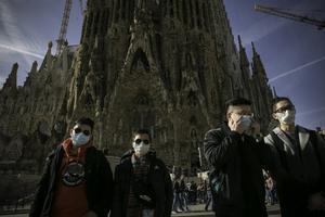 Gente con mascarillas haciendo turismo en la Sagrada Familia de Barcelona