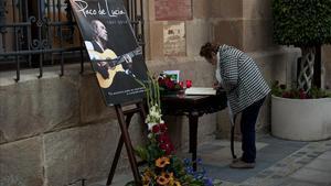 Una mujer firma en el libro de condolencias frente a un fotografía de Paco de Lucía en Algeciras