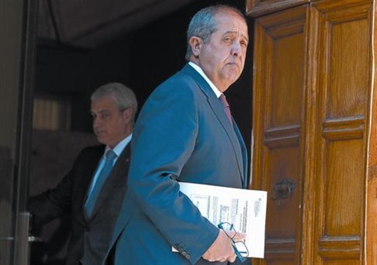 El 'conseller' de Empresa, Felip Puig, pasa ante el titular de Justícia, Germà Gordó, el 13 de marzo del 2012, en el Palau de la Generalitat.