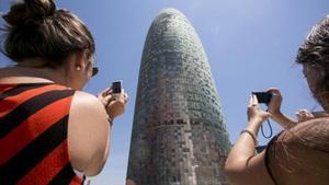 Dues turistes fotografien la torre Agbar.