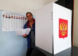 Una mujer sale de una cabina de votación con sus papeletas en un colegio electoral de Novoye Bobrenevo, pueblo de la región de Moscú.