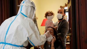 Un sanitario realiza test PCR a una familia en Roma.
