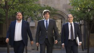 El 'president' Carles Puigdemont, entre el vicepresidente Oriol Junqueras y el 'conseller' Jordi Turull, en el Palau de la Generalitat.