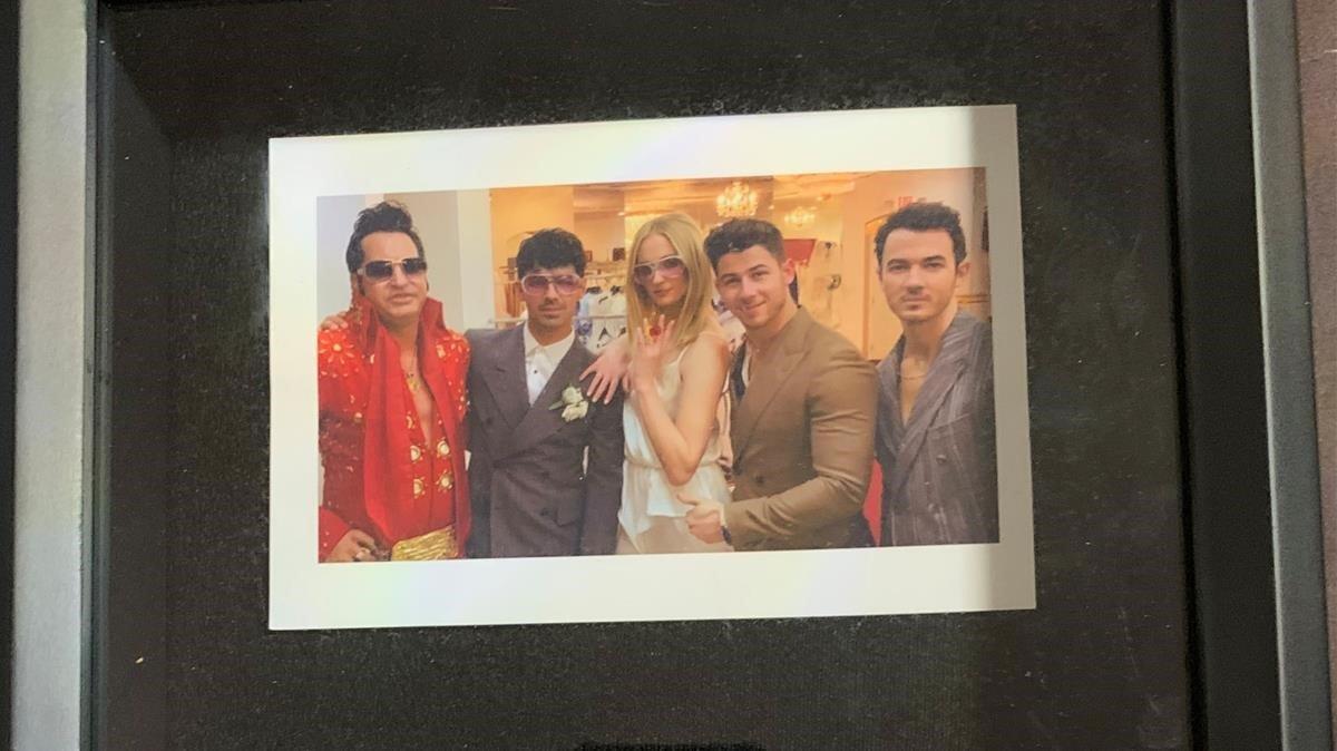 Detalle de la foto enmarcada de la boda de Joe Jonas y Sophie Turner, con el Elvis Presley que ofició la ceremonia y Kevin y Nick Jonas.