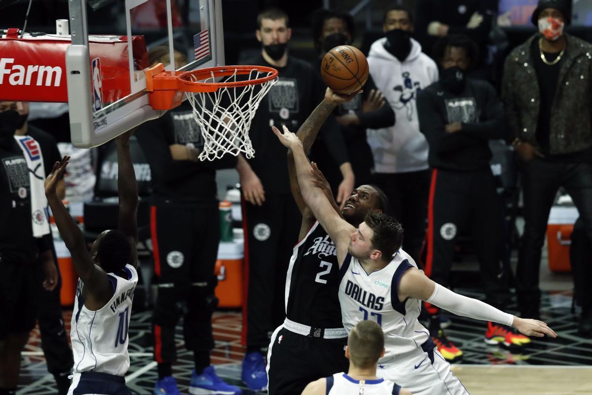 Kawhi Leonard intenta un lanzamiento ante la oposición de Luka Doncic en el partido entre Los Ángeles Clippers y Dallas Mavericks.