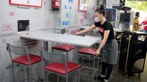 El IPC baja tres décimas en julio, hasta el -0,6%. En la foto, una empleada de un bar de Lleida prepara las mesas en el interior del local.