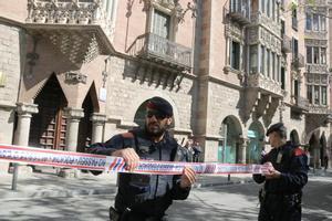 Dos agentes de los Mossos acordonan la zona mientras la Guardia Civil inspecciona la sede del Diplocat, durante un registro el pasado 12 de abril.