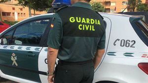 Un guardia civil, junto a un coche del instituto armado.