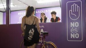 Informadores contra el acoso sexual amparado en el ocio nocturno atienden en un estand en Barcelona.