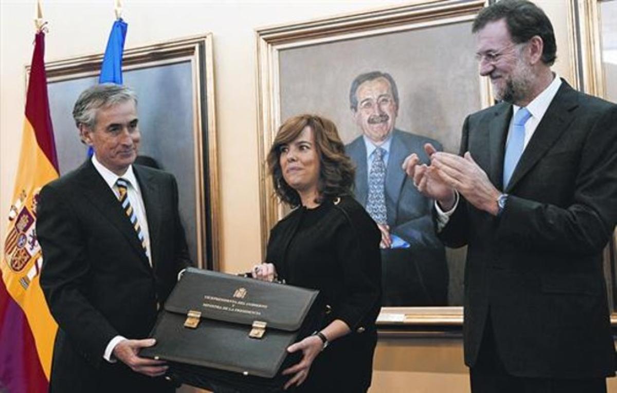 Sáenz de Santamaría recibe la cartera de manos de Jáuregui, en presencia de Rajoy, ayer.