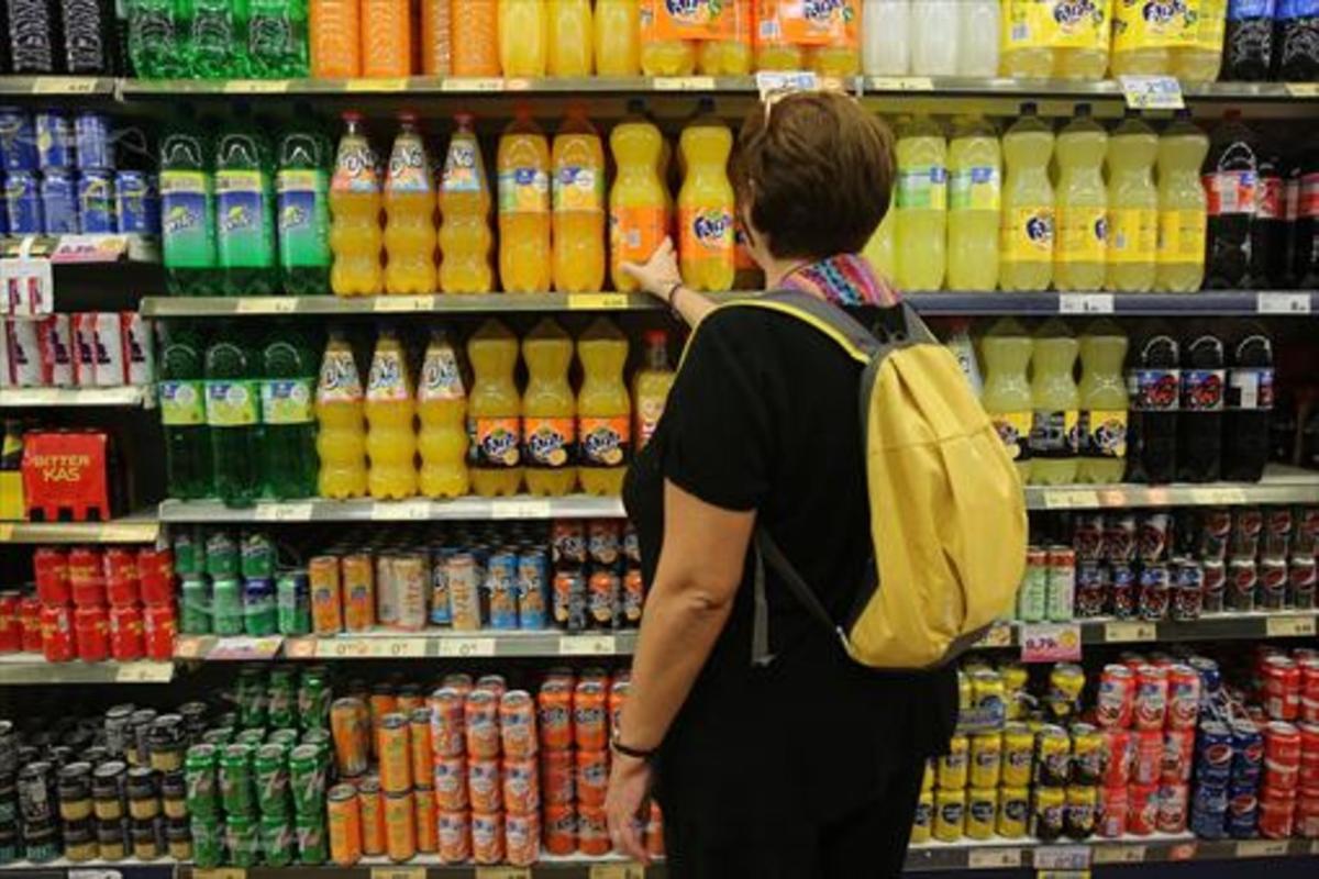 Una mujer ante las bebidas azucaradas de un supermercado.