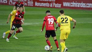 Simón, del Mirandés, controla un balón bajo la vigilancia de Bueno.