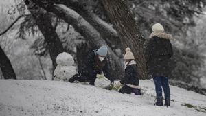 Tres personas juegan con la nieve el parque del Retiro.