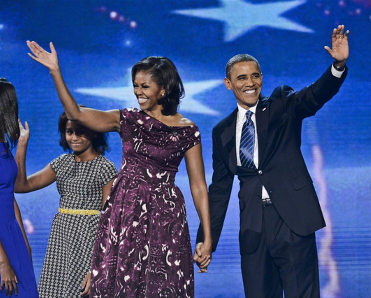 Barack Obama y su esposa, Michelle, saludan tras el discurso del presidente, anoche en Charlotte.