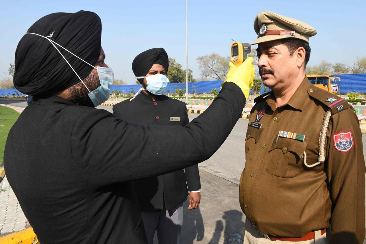 Miembros del personal de un hotel de Amritsar (India) toman la temperatura de un personal de la policía en la entrada del establecimiento, este domingo, para detectar si tiene coronavirus.