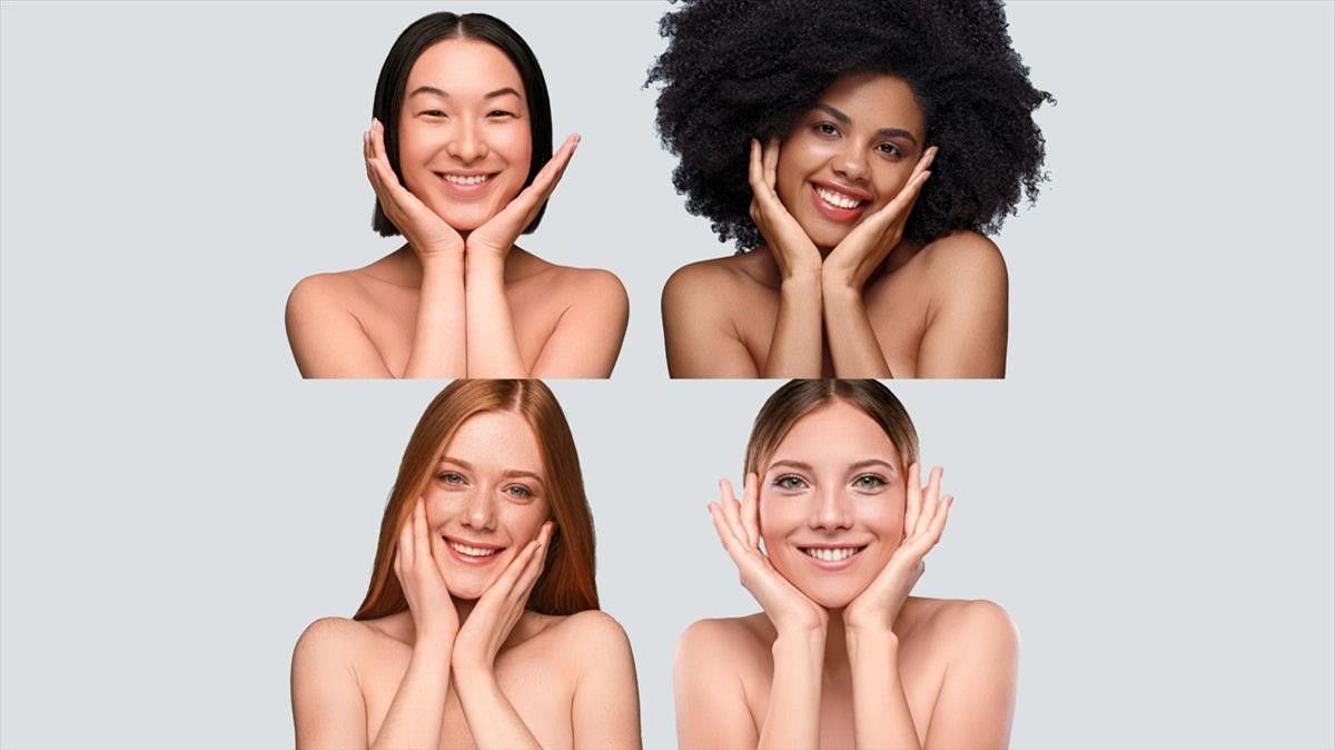 gente The Cool Skin    Optimistic multiethnic young ladies touching clean face skin and smiling for camera while representing cosmetology industry against blue background