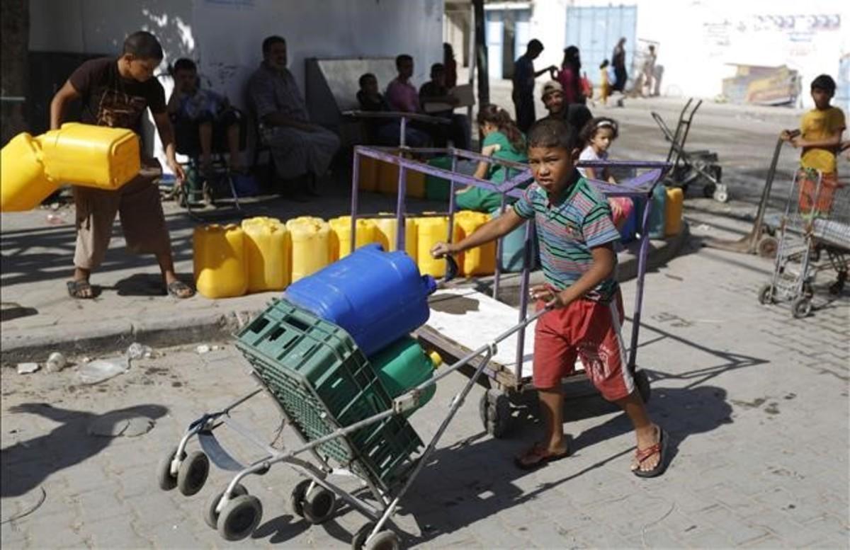 Palestinos cogen agua de un contenedor en Gaza en una imagen de archivo.