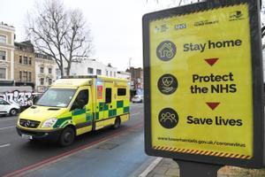Un ambulancia pasa junto a un cartel urbano con consignas sobre las precauciones contra el covid-19.
