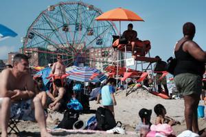 Un grupo de gente se refresca en la playa de Coney Island, en Brooklyn, en uno de los días más calurosos del año, en Nueva York.