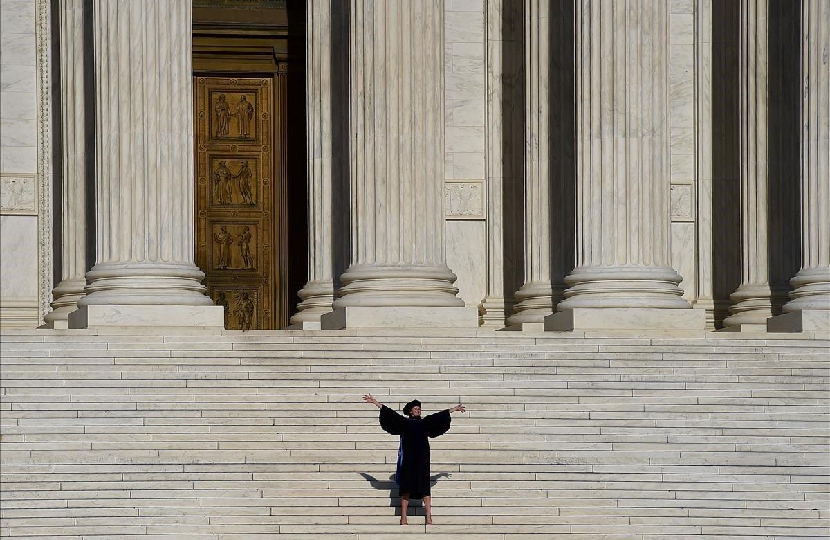 Un graduado posa en los escalones de la Corte Suprema cuando las ceremonias de graduación en todo el país se cancelan debido a la pandemia de coronavirus.