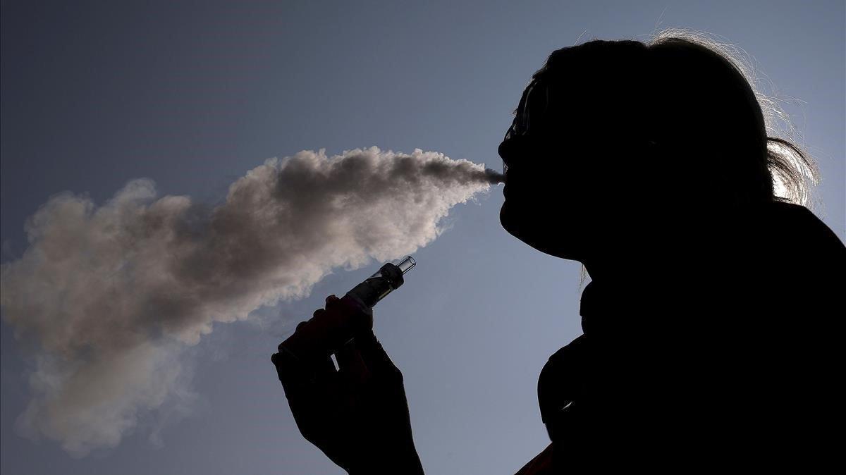 Una mujer exhala el vapor de un cigarrillo electrónico.