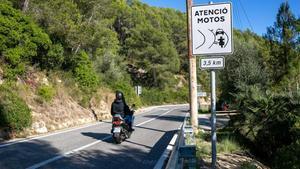 Una moto pasa al lado de una señal que avisa de las nuevas marcas en la calzada en la carretera del pantano de Foix.