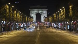 La avenida de los Campos Elíseos, con el Arco de Triunfo al fondo, casi vacía durante las horas del toque de queda en París.