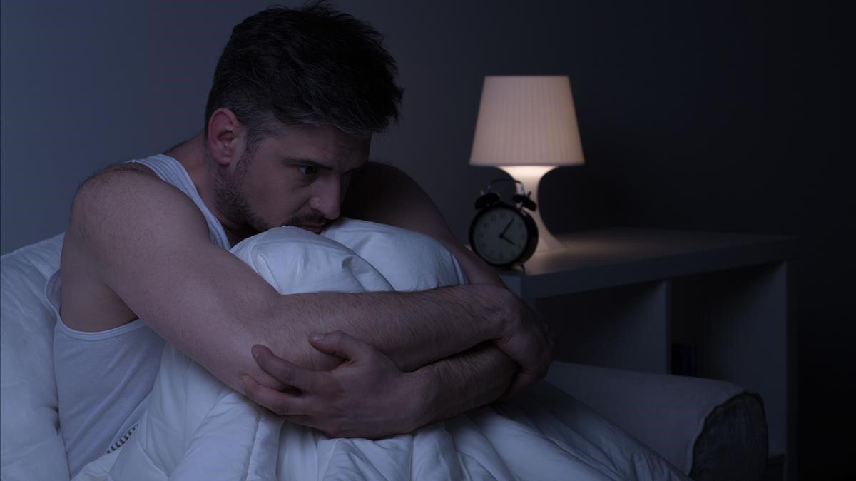 Hombre preocupado con ansiedaden la cama.
