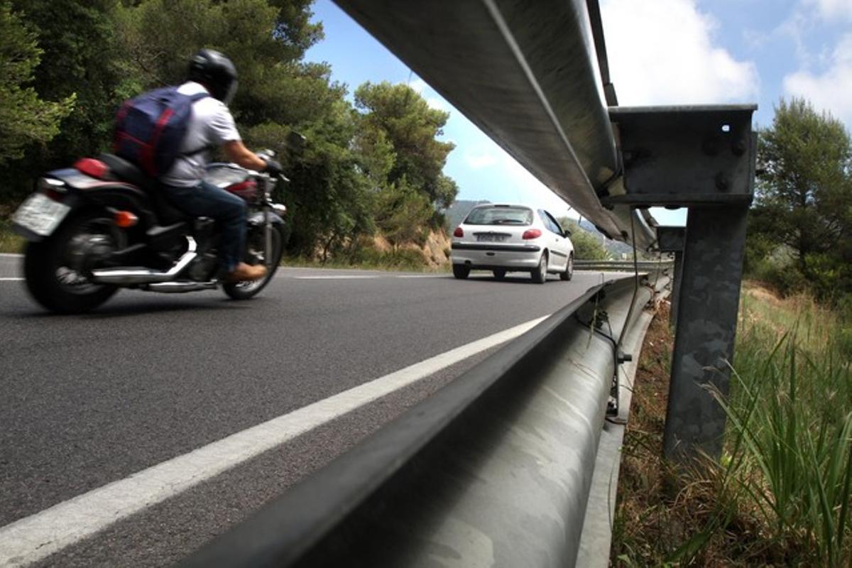 Una moto circula por la sinuosa carretera entre Tossa de Mar y Lloret.